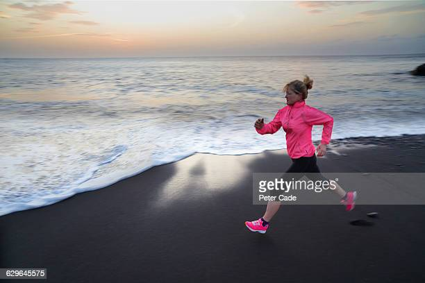 woman running on beach - jogging stock pictures, royalty-free photos & images