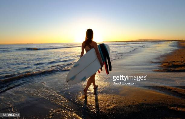 woman running on beach with surfboard at sunset - seal beach stock pictures, royalty-free photos & images