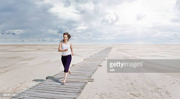 Woman running on boardwalk, Sankt Peter Ordings, Schleswig Holstein, Germany