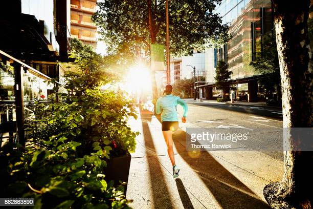 Woman running on city sidewalk during early morning workout