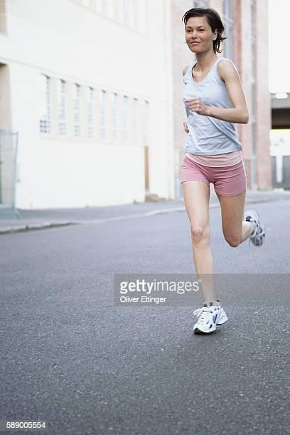 woman running on city street - oliver eltinger stock-fotos und bilder