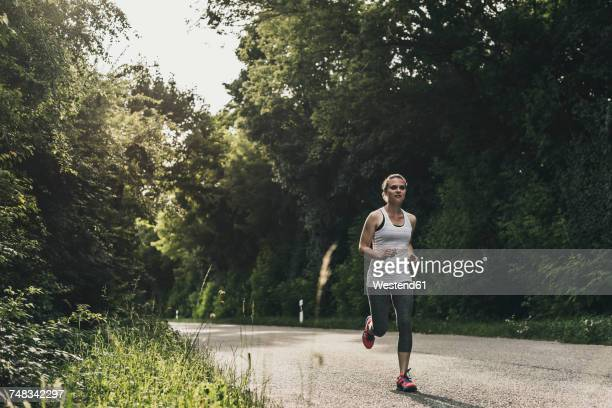 woman running on country road - joggeuse photos et images de collection