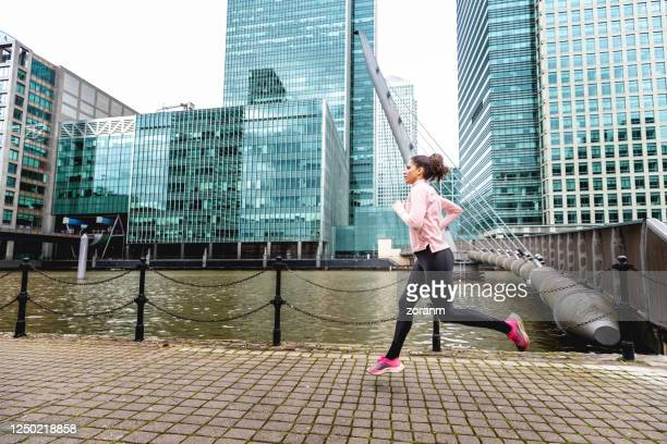 woman running on empty city street during workout - active lifestyle stock pictures, royalty-free photos & images