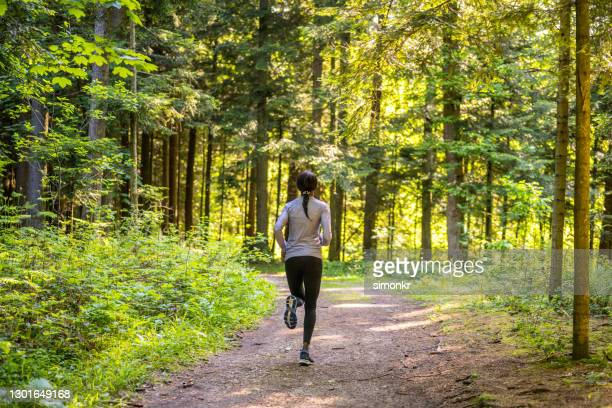 woman running on footpath in forest - active lifestyle stock pictures, royalty-free photos & images