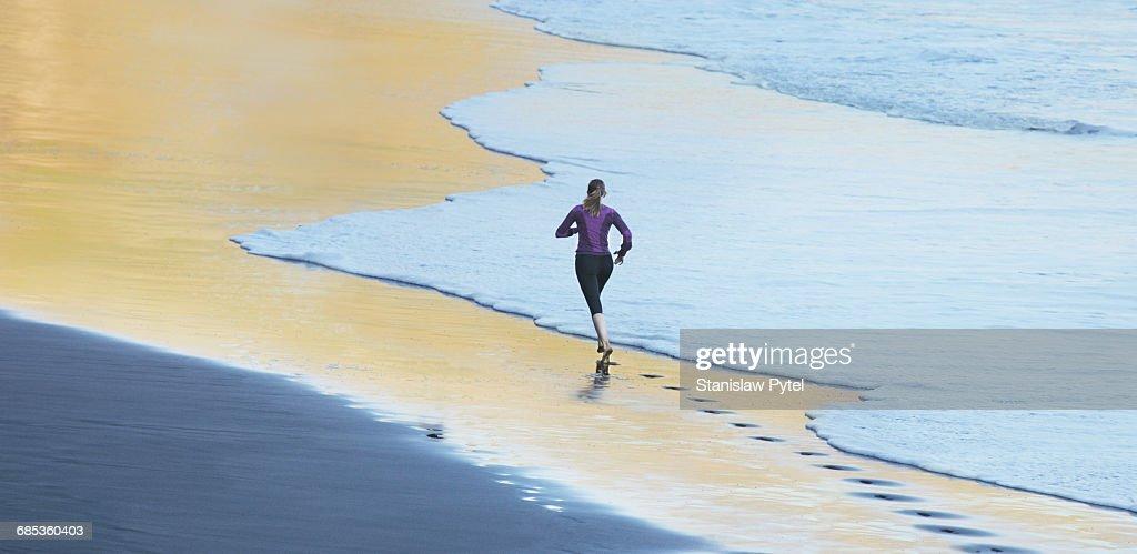 Woman running on gold beach : Stock Photo