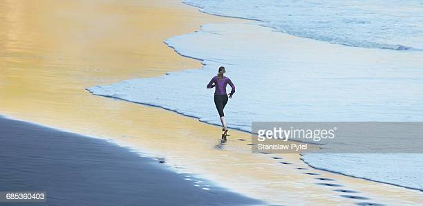 Woman running on gold beach