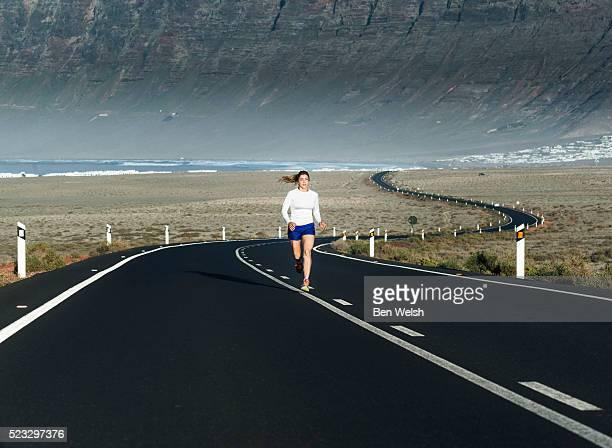 woman running on highway, famara, lanzarote, canary islands, spain - isla de lanzarote fotografías e imágenes de stock