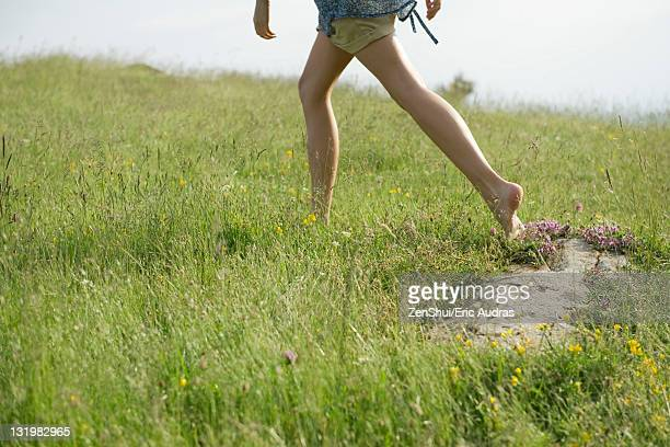 woman running on meadow with bare feet, low section - pieds nus photos et images de collection