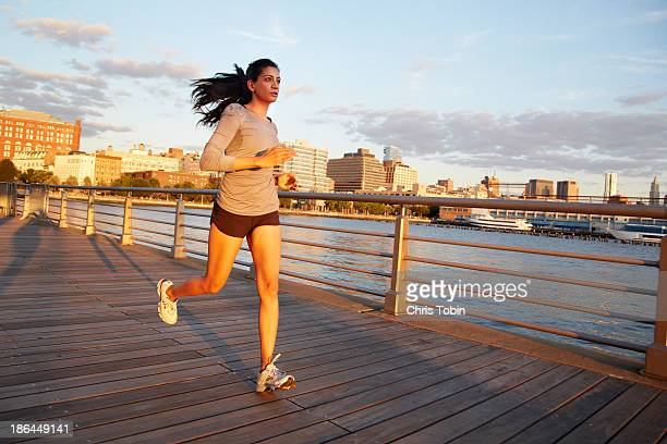 Woman running on pier at sunset in a city