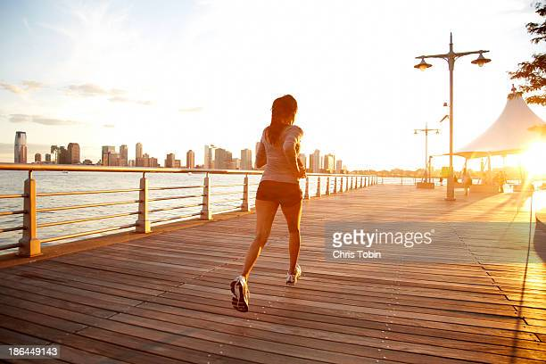 Woman running on pier at sunset in the city