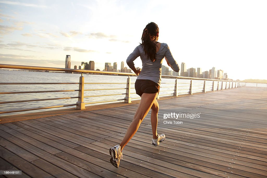 Woman running on pier in front of city skyline : Stock Photo