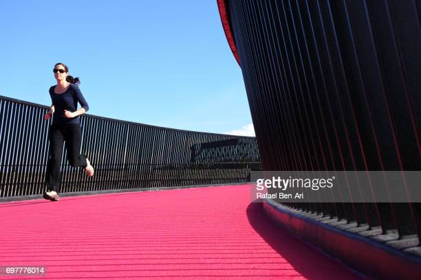 woman running on pink cycleway in auckland new zealand - rafael ben ari stock pictures, royalty-free photos & images