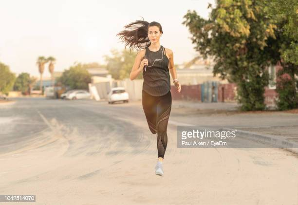 woman running on road against sky - aikāne stock pictures, royalty-free photos & images