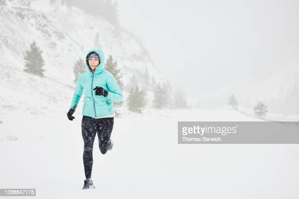 woman running on road during winter snow storm - forward athlete stock pictures, royalty-free photos & images