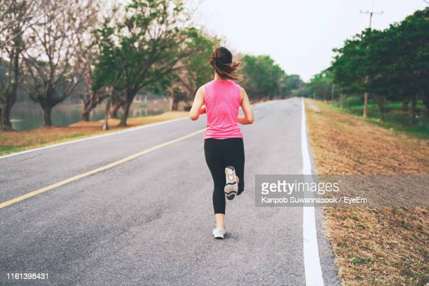 woman running on road - joggeuse photos et images de collection