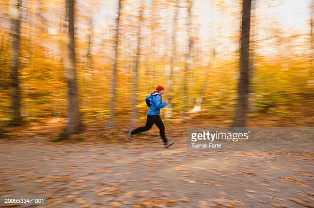 Woman running on road through forest, side view