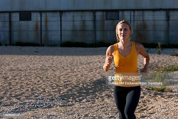 Woman running on rocky beach