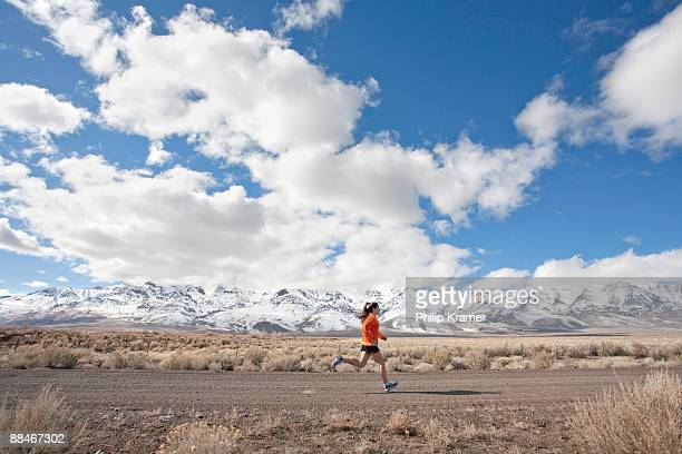 woman running on rural road in mountains. - steens mountain stock pictures, royalty-free photos & images