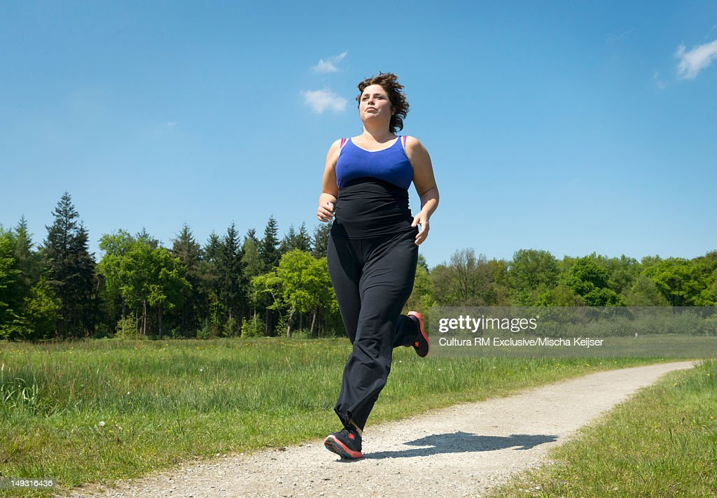Woman running on rural road : Stock Photo