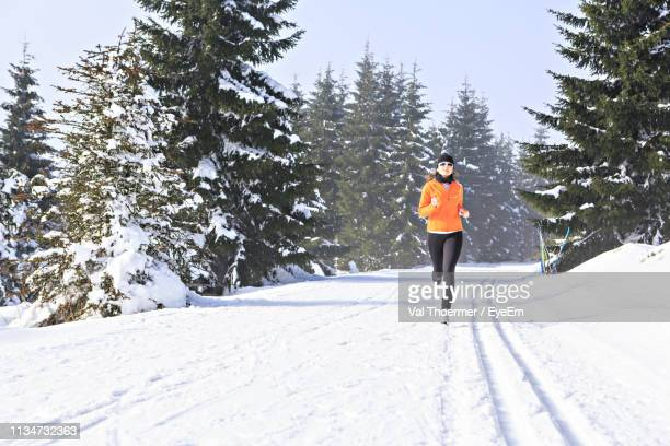 woman running on snow covered field against sky - val thoermer stock-fotos und bilder