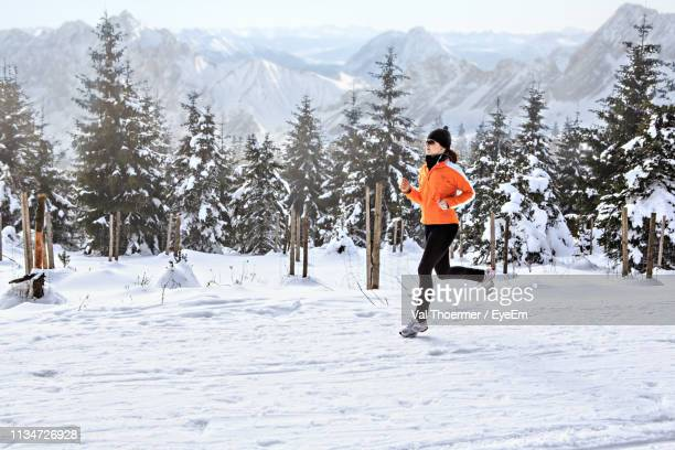 woman running on snow covered field against trees - val thoermer stock-fotos und bilder