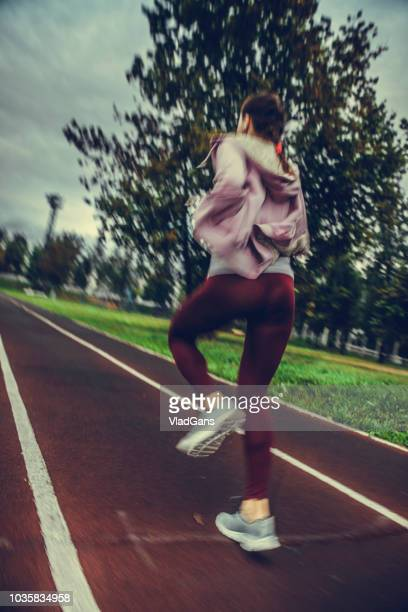 woman running on stadium - vladgans or gansovsky stock pictures, royalty-free photos & images