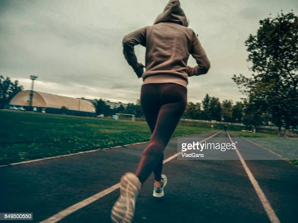 woman running on stadium track - vladgans or gansovsky stock pictures, royalty-free photos & images