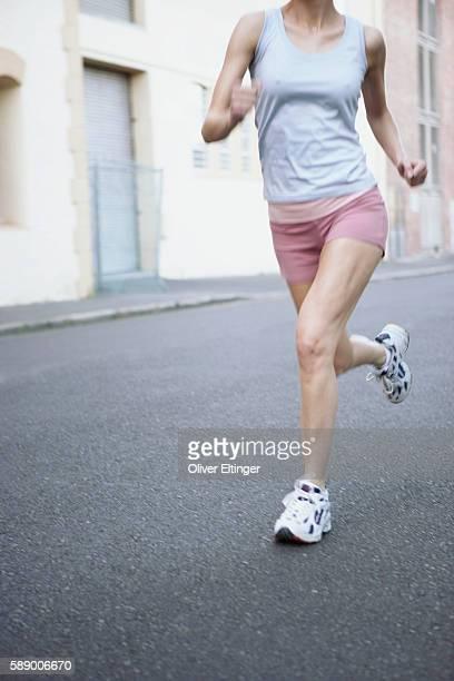 woman running on street - oliver eltinger stock-fotos und bilder