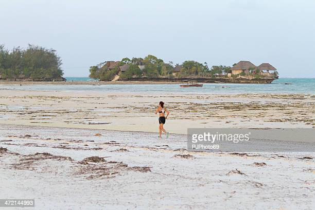 Woman running on the beach at low tide - Zanzibar