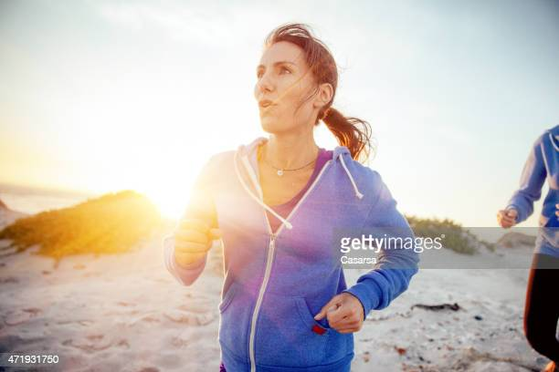 woman running on the beach - 40 44 jaar stockfoto's en -beelden