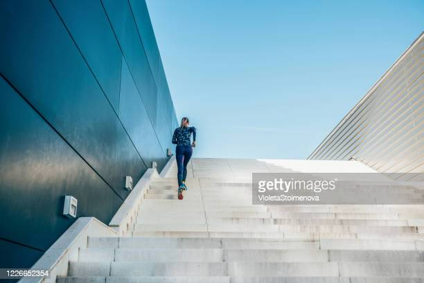 woman running on the city stairs. - staircase stock pictures, royalty-free photos & images