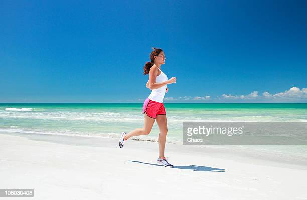 woman running on the water edge at the beach - running shorts stock pictures, royalty-free photos & images