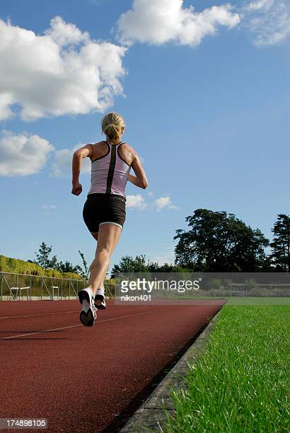 woman running on track - striding stock pictures, royalty-free photos & images