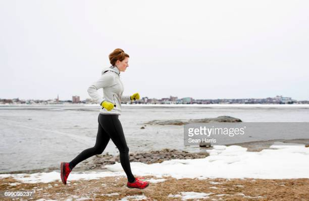 woman running on trail around back cove - portland maine stock pictures, royalty-free photos & images