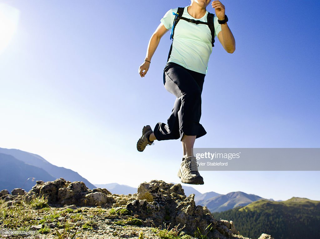 Woman running on trail in mountains, low section : Foto stock