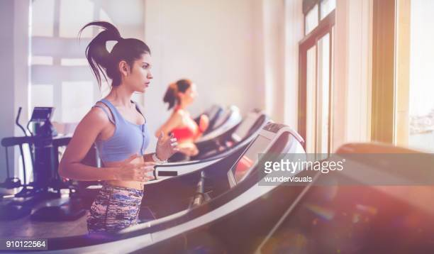 Woman running on treadmill and keeping fit