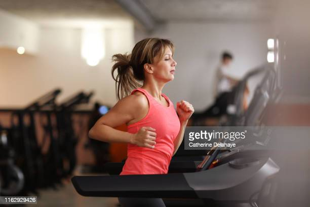 woman running on treadmill at fitness center - palestra club ginnico foto e immagini stock