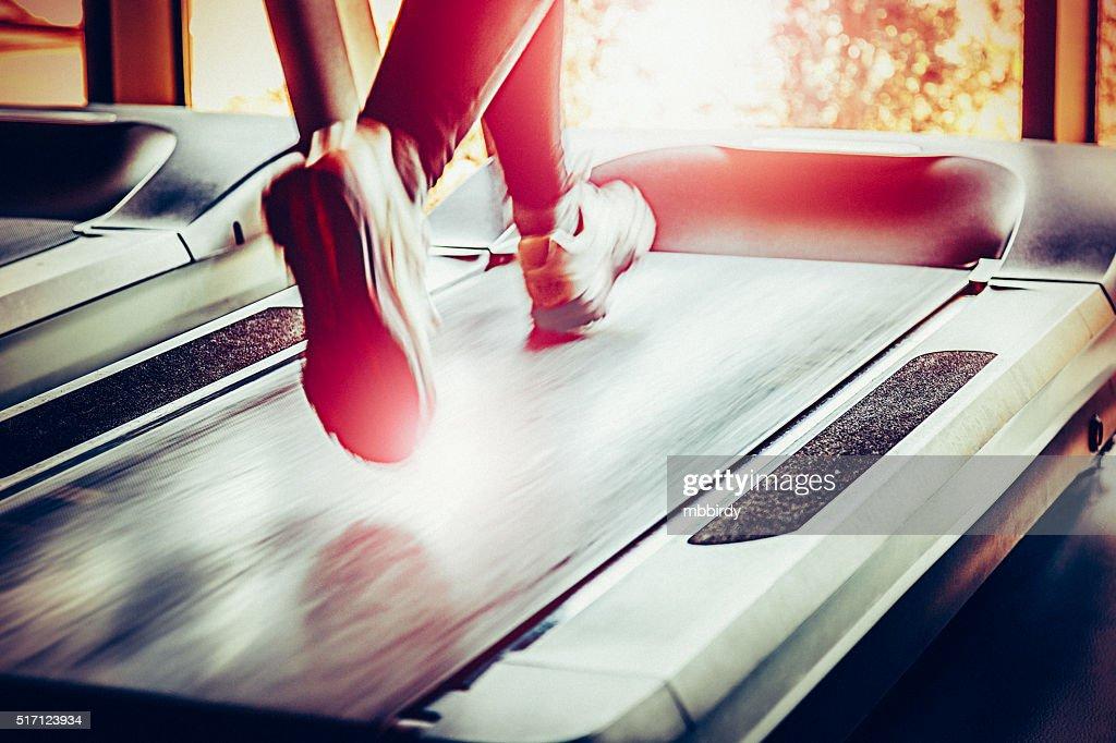 Woman running on treadmill : Stock Photo