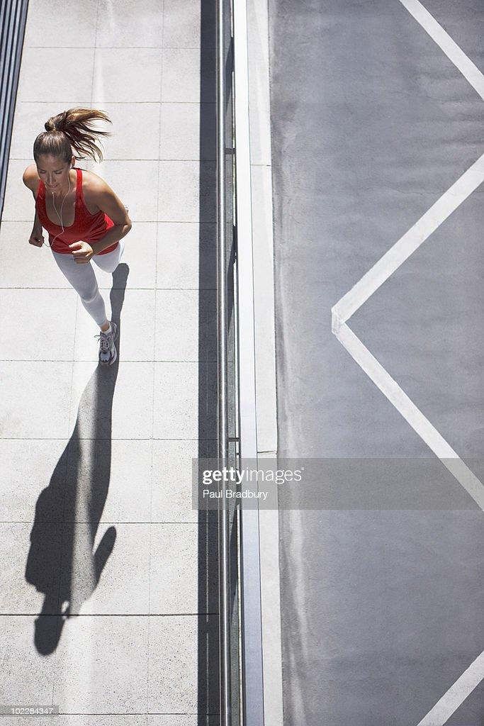 Woman running on urban sidewalk : Stock Photo