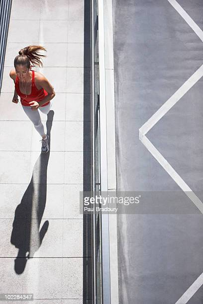 woman running on urban sidewalk - vertical stock pictures, royalty-free photos & images
