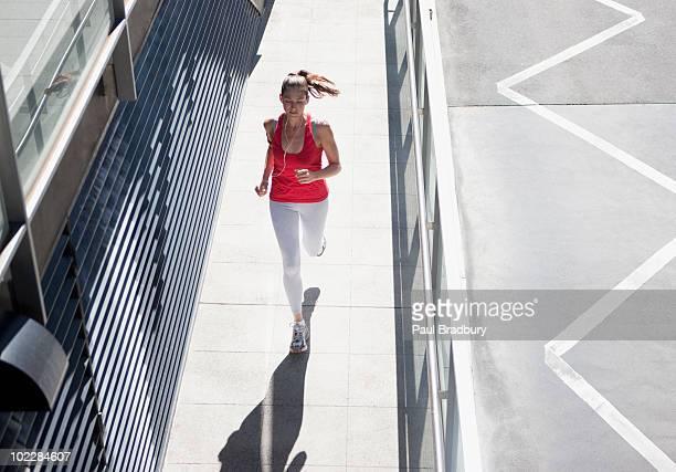 Woman running on urban sidewalk