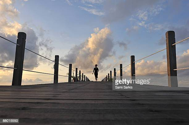 woman running on wooden jetty, at sunrise - mabul island stock photos and pictures