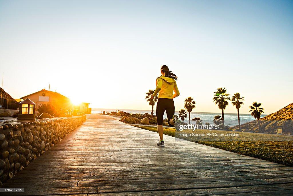 Woman running on wooden path : Stock Photo