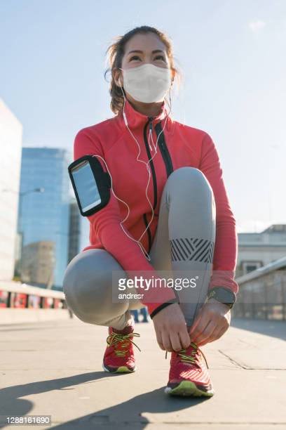 woman running outdoors and tying her shoelace and wearing a facemask - state of emergency stock pictures, royalty-free photos & images