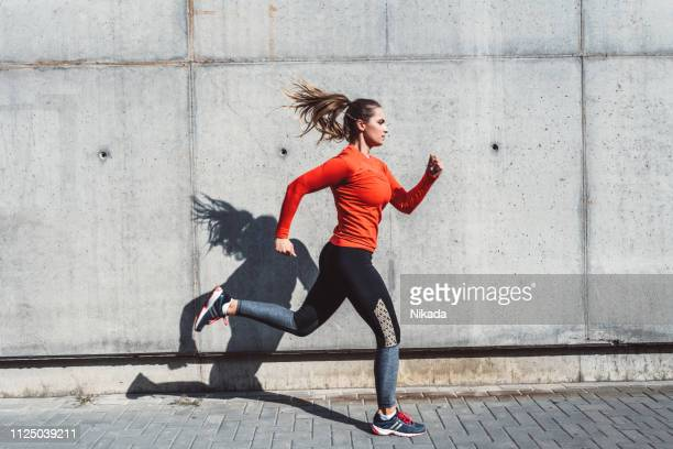woman running outdoors in the city - running stock pictures, royalty-free photos & images