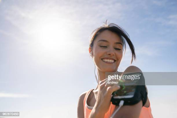 woman running outdoors using cell phone on an arm band - arm band stock pictures, royalty-free photos & images