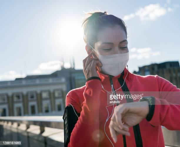 woman running outdoors using wearable technology and a facemaks - state of emergency stock pictures, royalty-free photos & images