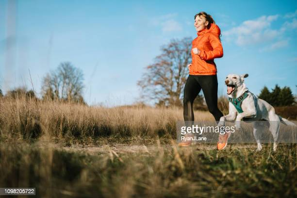 Woman Running Outdoors With Pet Dog