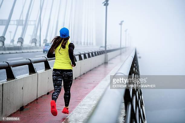 Woman running over the bridge
