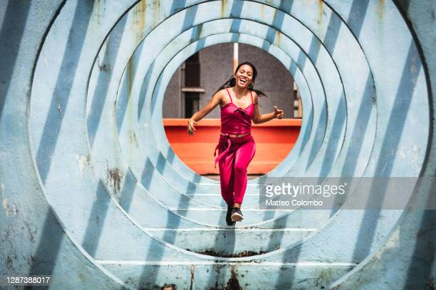 woman running through circle shaped structure, hong kong - jumping stock pictures, royalty-free photos & images